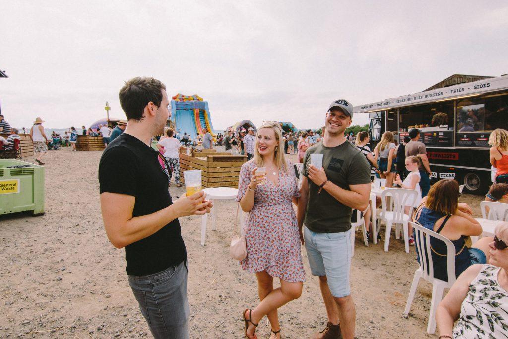 Happy festival goers enjoy a drink in the sun